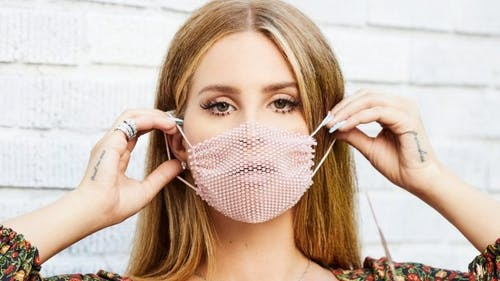 Lana Del Rey has been almost unrecognizable to her long-time fans after pictures revealed her to be posing with bleach blonde hair and a netted mask.  – Photo by Twitter