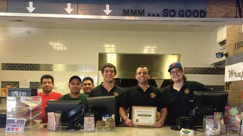 Hansel 'n Griddle owner Nicholas Komandis and his staff pose alongside a certificate awarded to them by The Daily Targum after their restaurant were winners in the first edition of March Munchies. – Photo by Brian Fonseca
