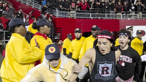 Michael Troglio (center) and Matthew Biscaldi (right), School of Arts and Sciences sophomores, were the first to plow past security guards and rush the football field last Saturday after Rutgers football's win against Michigan State. – Photo by Photo by Shawn Smith | The Daily Targum