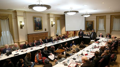 """Students sat in during the Board of Governors meeting on Dec. 6, demanding that Rutgers call itself a """"sanctuary campus."""" Earlier during the meeting, University President Robert L. Barchi called the school a """"safe haven"""" for undocumented students. – Photo by Photo by Dimitri Rodriguez 
