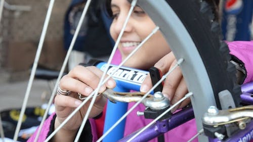 Rewa Marathe, a Graduate Student Association representative, adjusts the brakes on a bike at GSA's second annual Bike Fair yesterday on the College Avenue campus. – Photo by Paul Solin